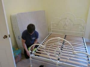 movers Manchester man disassembling a white bed frame image 02