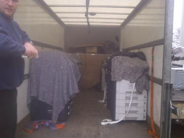 Photocopy machines secured and strapped in place with Movers Manchester man looking on