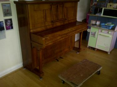 A vintage wooden piano ready to be moved in Manchester House