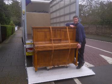 A vintage wooden piano strapped & ready to be mounted on removal van with mover standing next to it in front of the van
